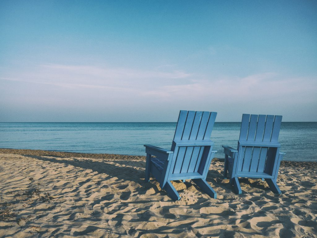 Image of two empty blue beach chairs sat on white sand facing out toward a calm sea