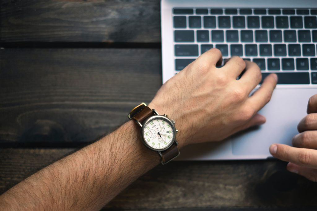 Person looking down to check the time on their watch while working at a laptop