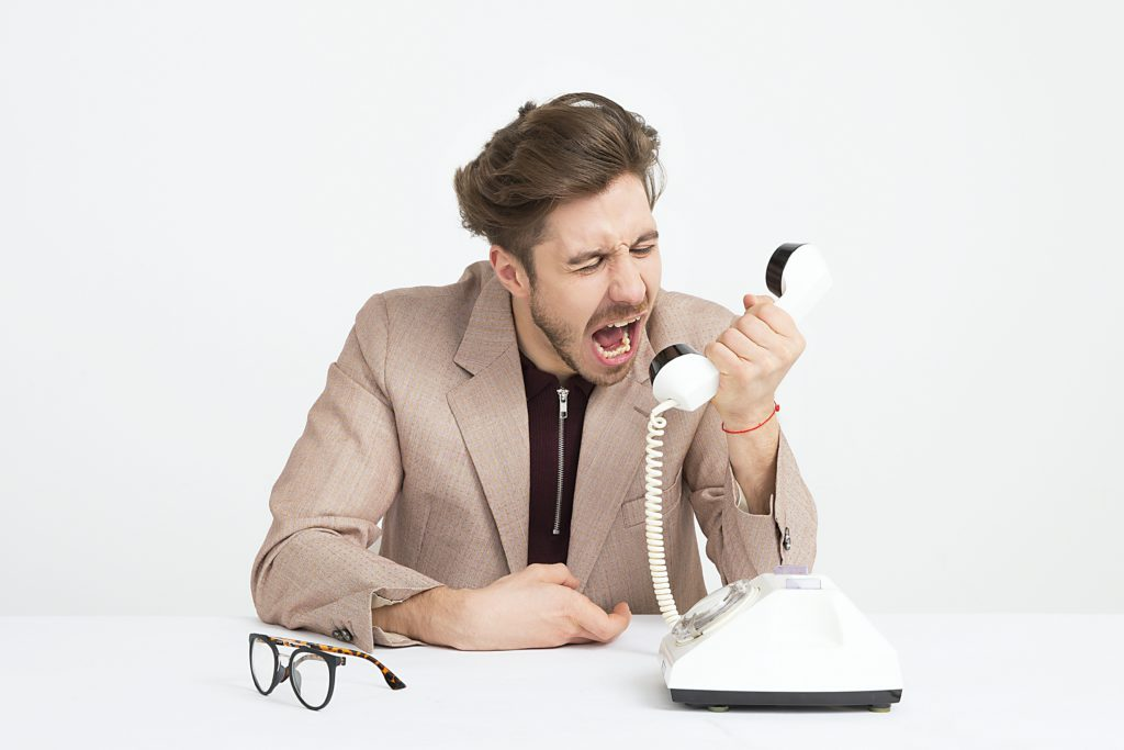 Man shouting into desk phone.