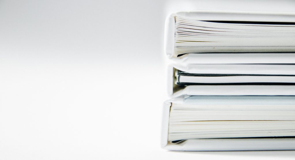 Two stacked white folders, on a white background, giving the impression of an accurate payroll process