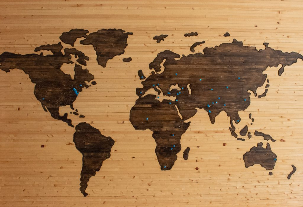 A world map painted into a wooden panelled background, with blue pins marking various locations