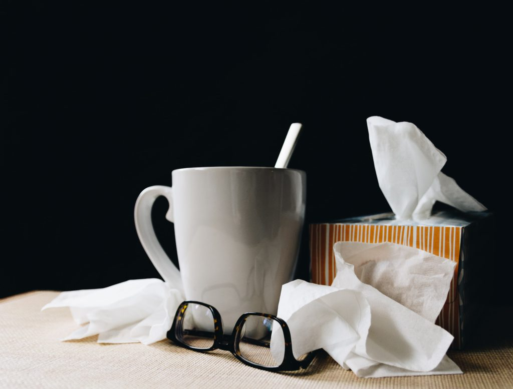 Sick leave paraphernalia; a large white mug, pair of glasses, and a tissue box surrounded by discarded tissues